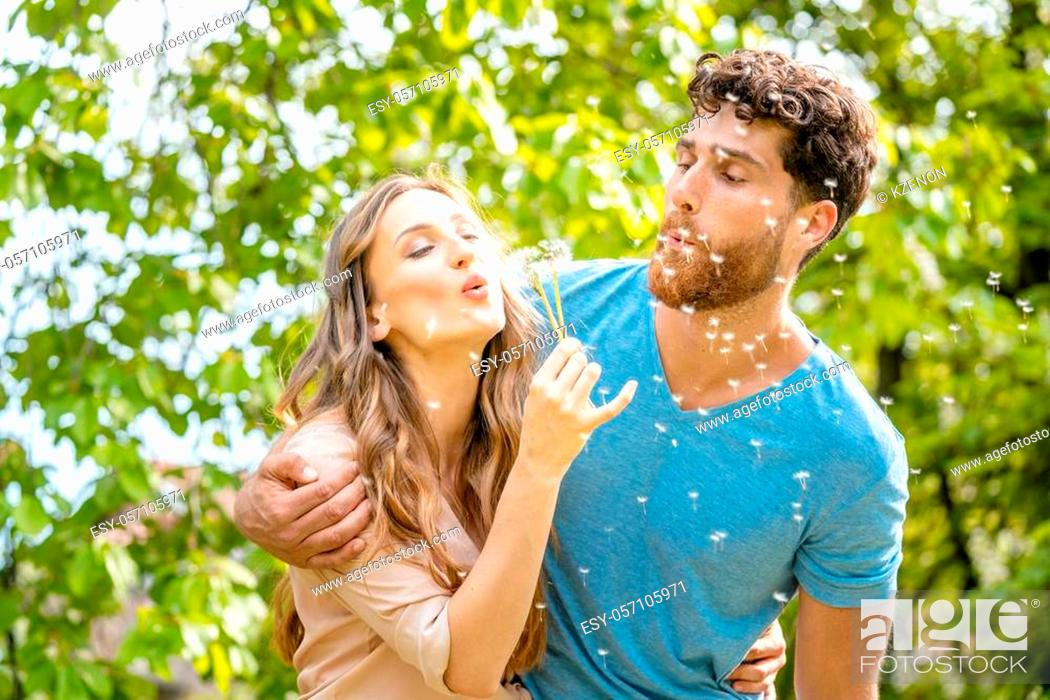 Stock Photo: Young couple daydreaming about their future blowing dandelion seeds being visibly happy.