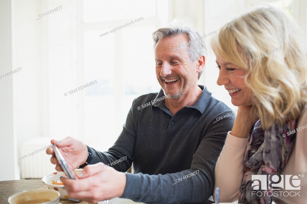 Stock Photo: Smiling mature couple using smart phone.