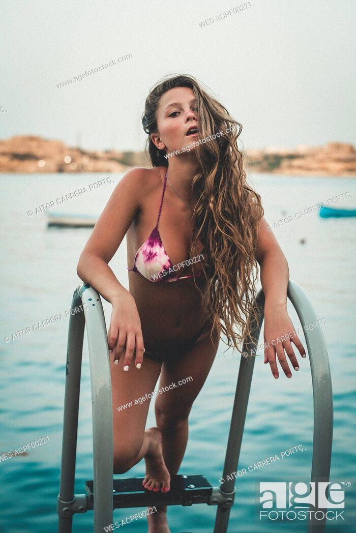 Stock Photo: Teenage girl in sexy bikini, standing on ladder to the sea.