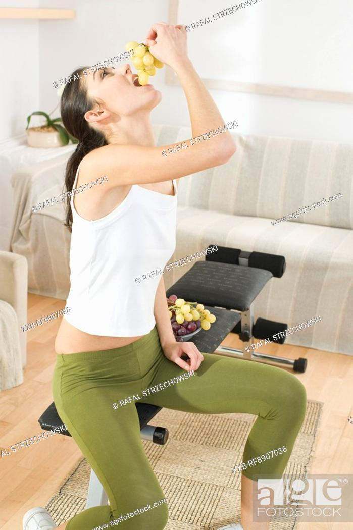 Stock Photo: young woman eating grapes.
