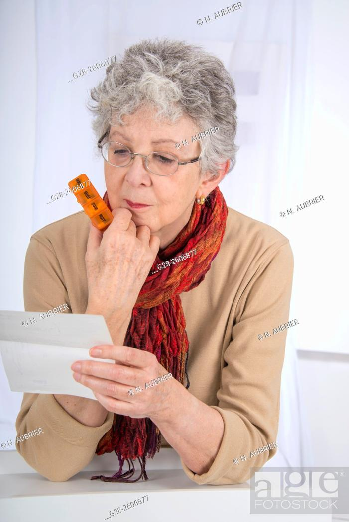 Stock Photo: Senior woman with grey hair, holding and reading a prescription, in one hand, and holding a 7 day pill reminder in the other hand.