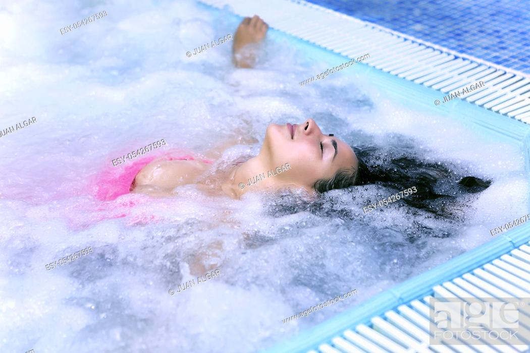 Stock Photo: Young woman with eyes closed in pool with air bubbles. Horizontal indoors shot.
