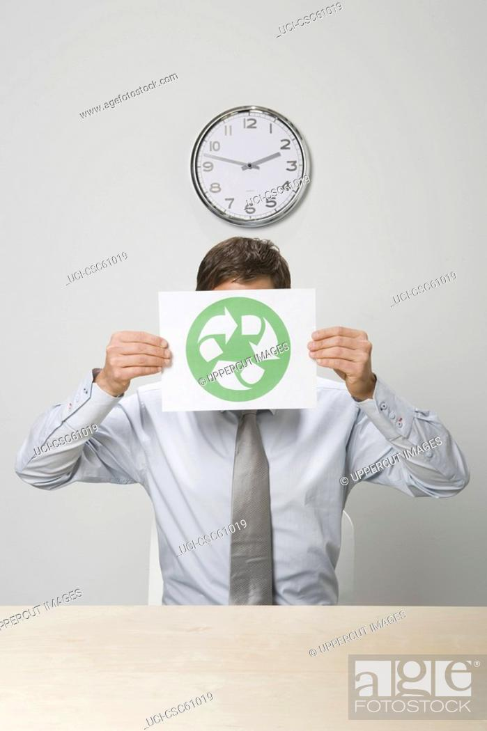 Stock Photo: Businessman holding recycling sign in front of face.