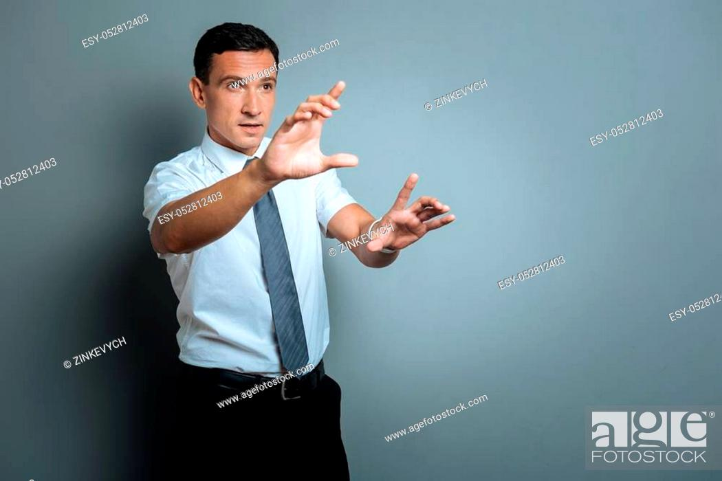 Stock Photo: Creative person. Nice positive smart man explaining his ideas and gesticulating while standing against grey background.