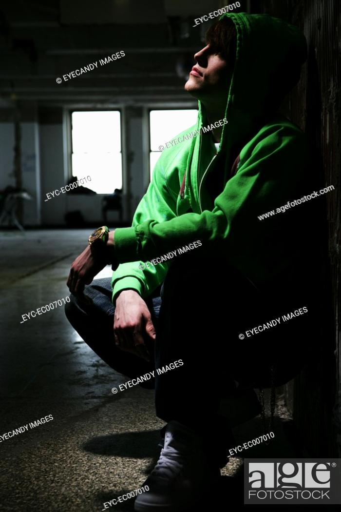 Stock Photo: Young man crouched down.