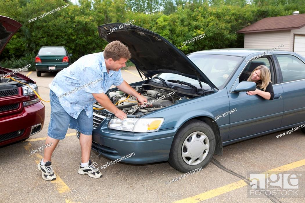 Stock Photo: A man helps boost the car battery of a woman's car in a parking lot, edmonton alberta canada.