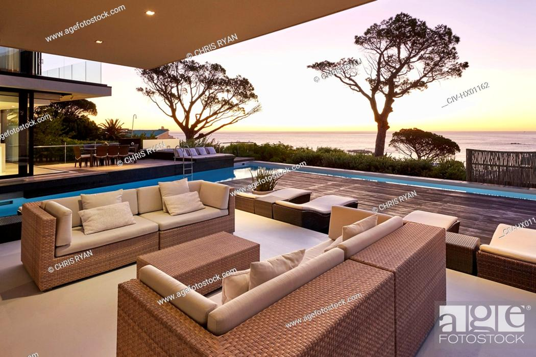 Stock Photo: Modern luxury home showcase patio and swimming pool overlooking ocean view at sunset.