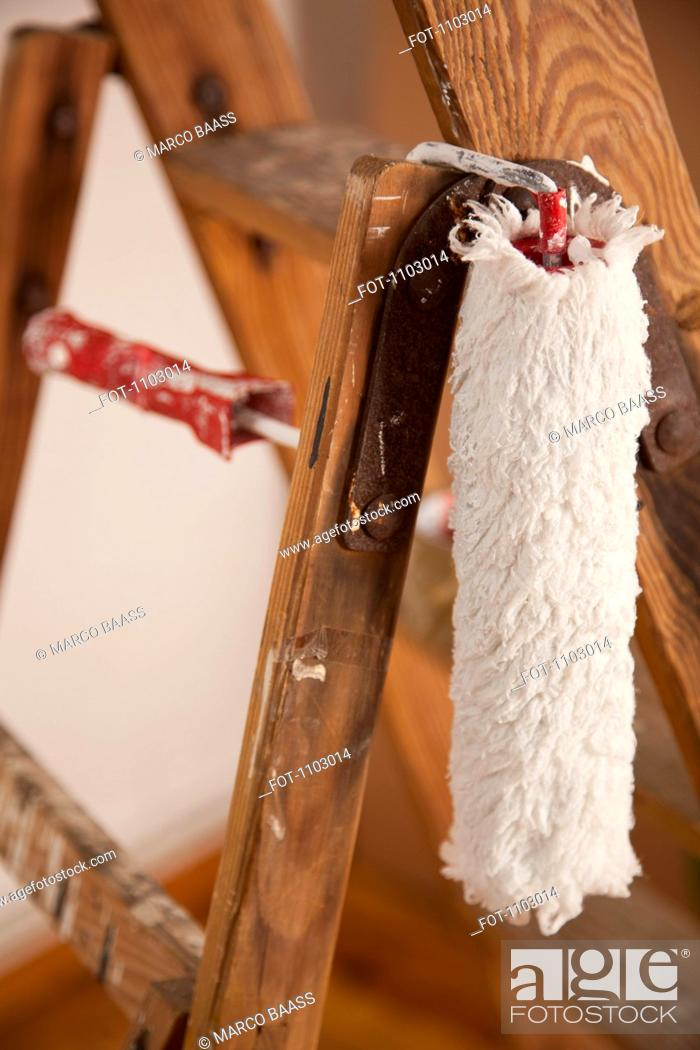 Stock Photo: A paint roller hanging from a wood step ladder, close-up.