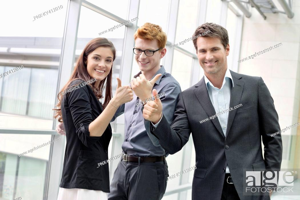 Stock Photo: Business executives showing thumbs up and smiling in an office.