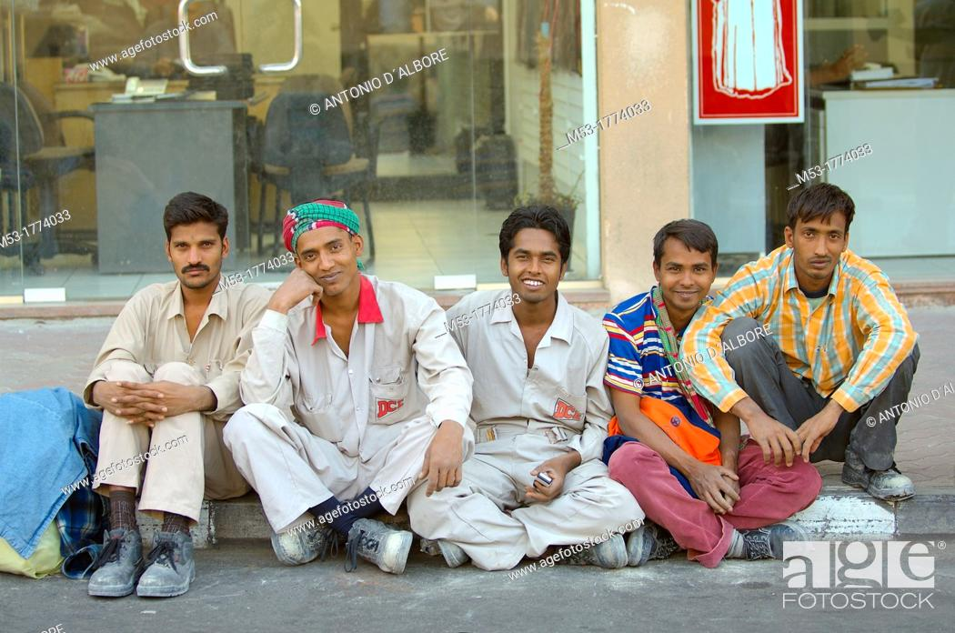 Stock Photo: male workers lined up on a street rest at the end of a working day  dubai  dubai  uae  middle east.