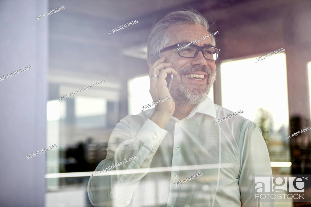 Stock Photo: Laughing businessman at the window talking on cell phone.
