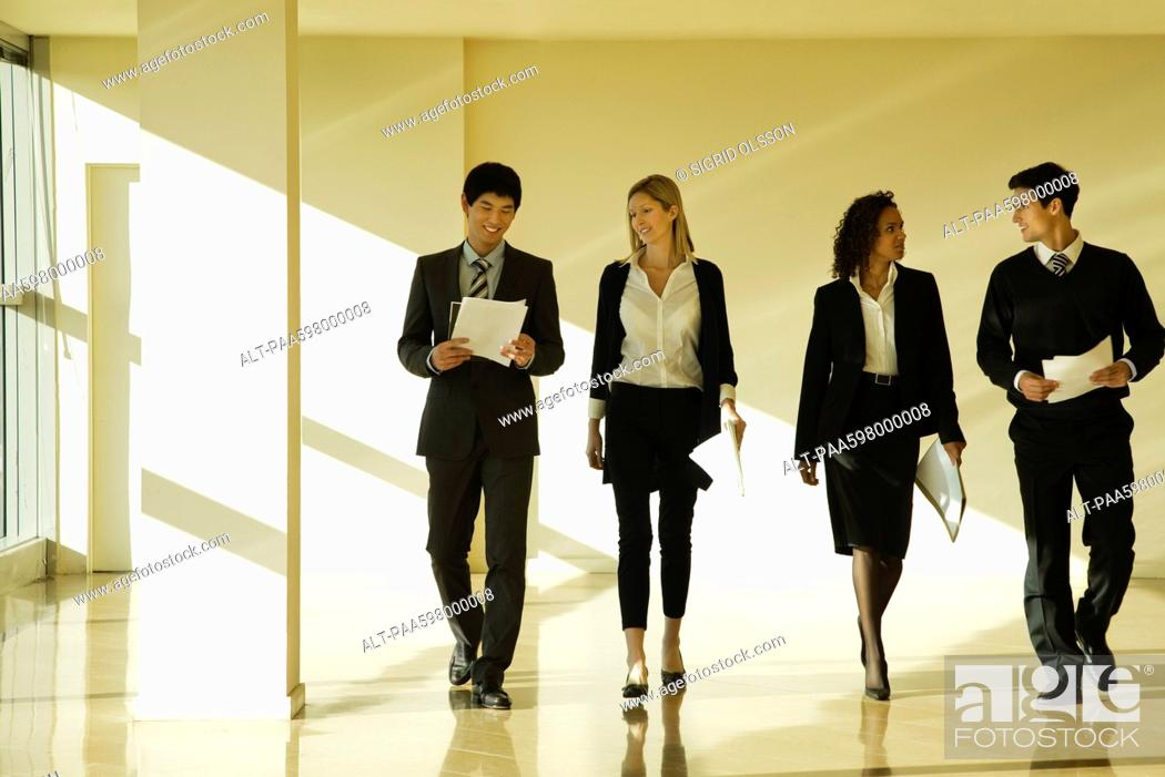 Stock Photo: Group of business associates talking as they walk together in lobby.