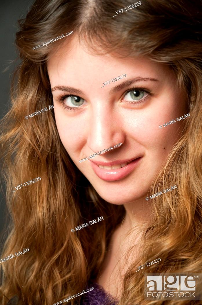Stock Photo: Portrait of young woman smiling and looking at the camera. Close view.