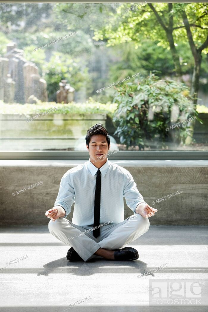 Stock Photo: A businessman taking a meditative break in a room full of indoor plants.