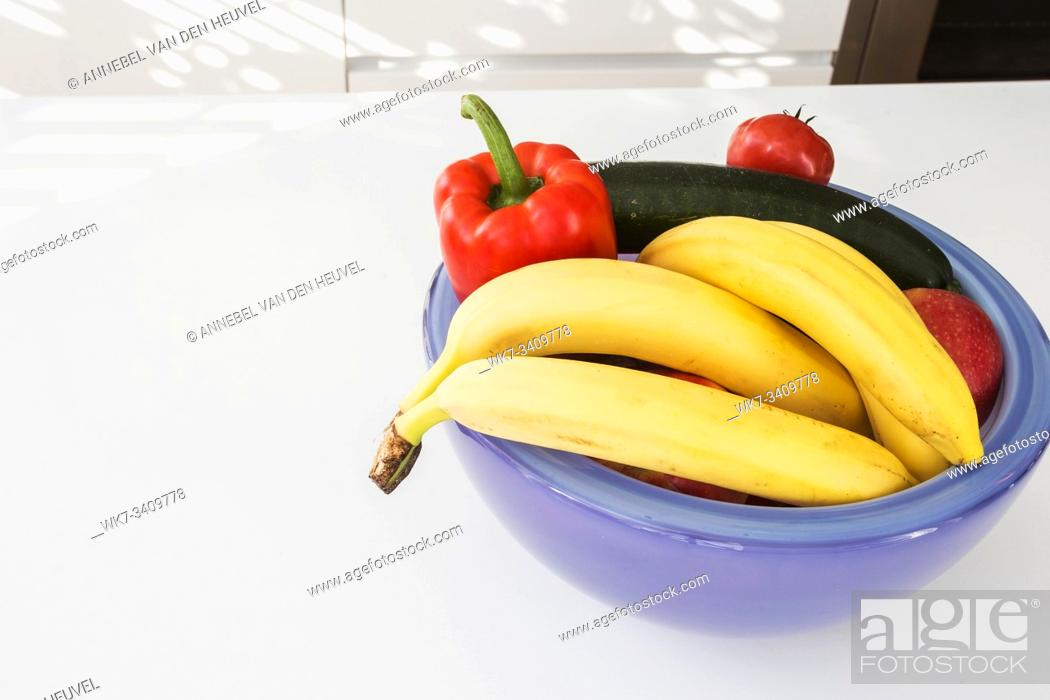 Stock Photo: Vegetables and fruit in a purple bowl on a white table closeup.