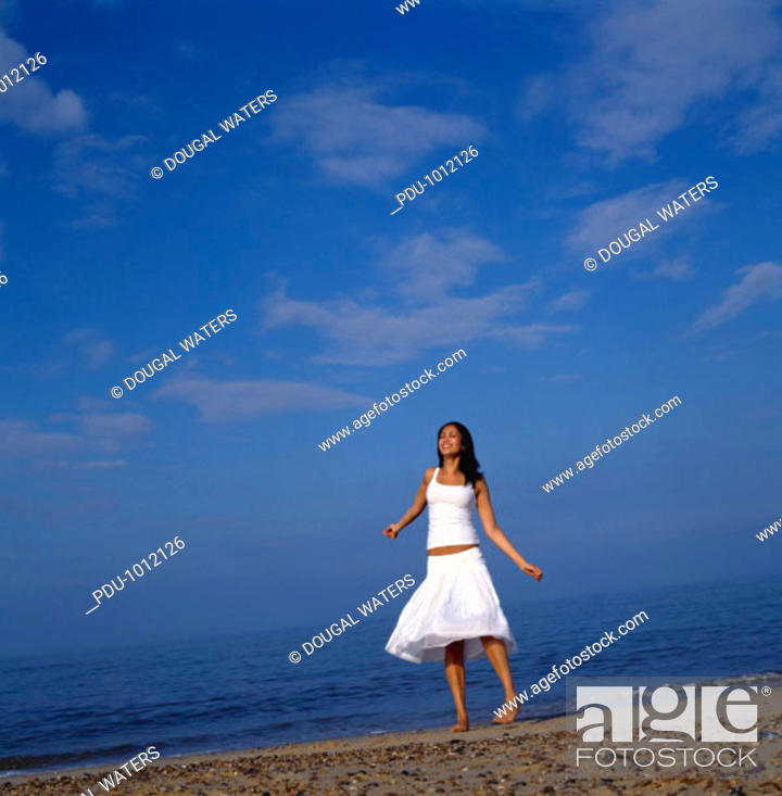 Stock Photo: Young woman spinning on sand at beach.