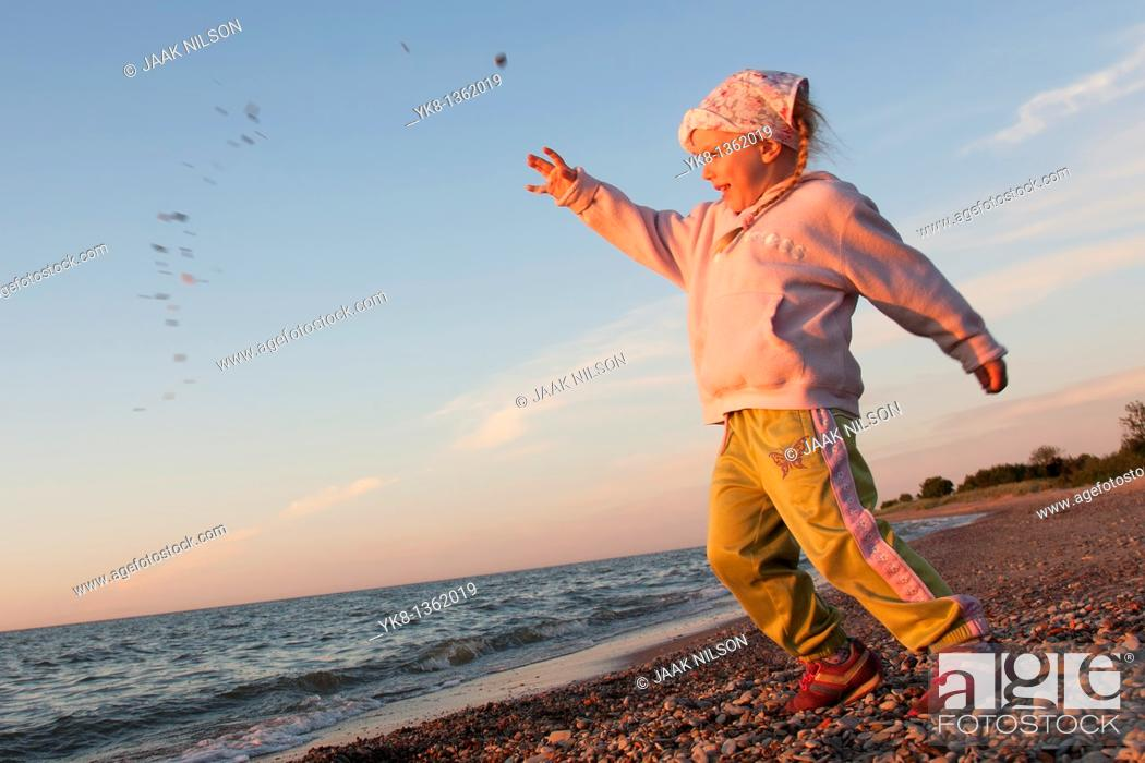 Stock Photo: Young Girl Throwing Stone into Water.