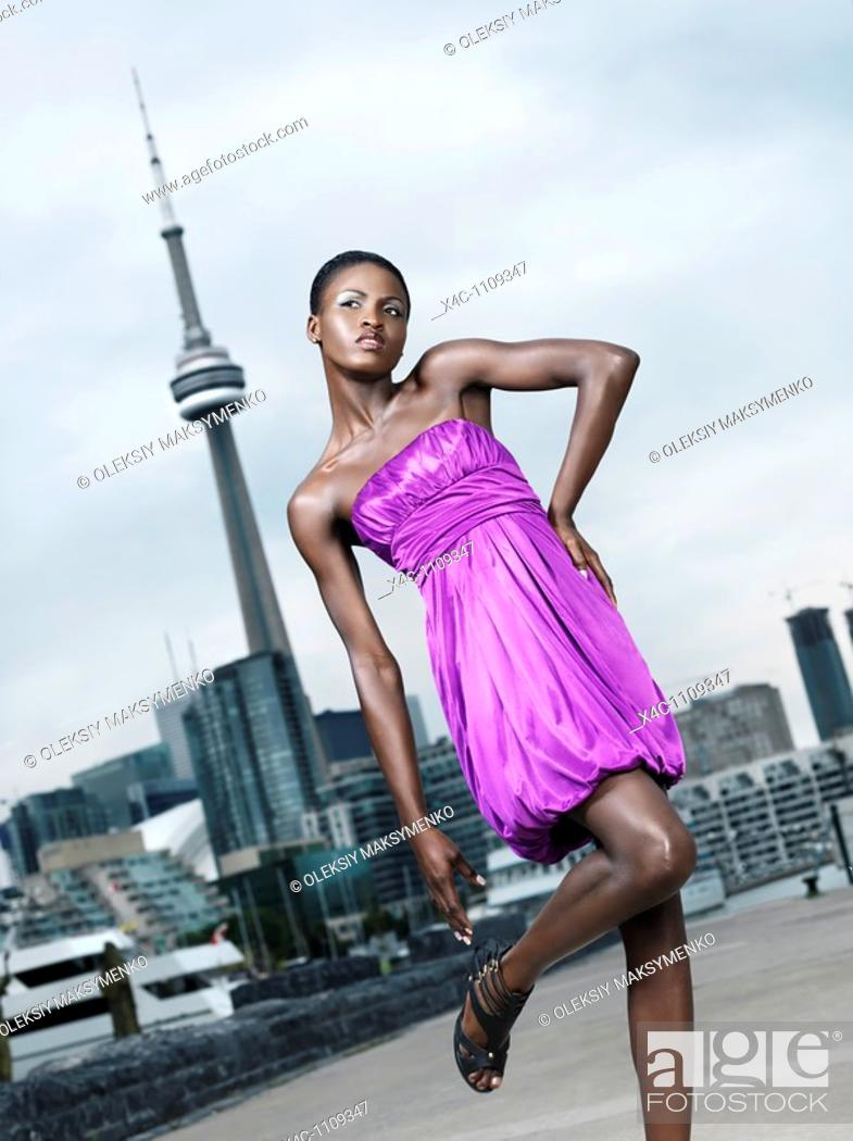 Stock Photo: Young woman fashion model posing in front of CN tower in Toronto, Canada.