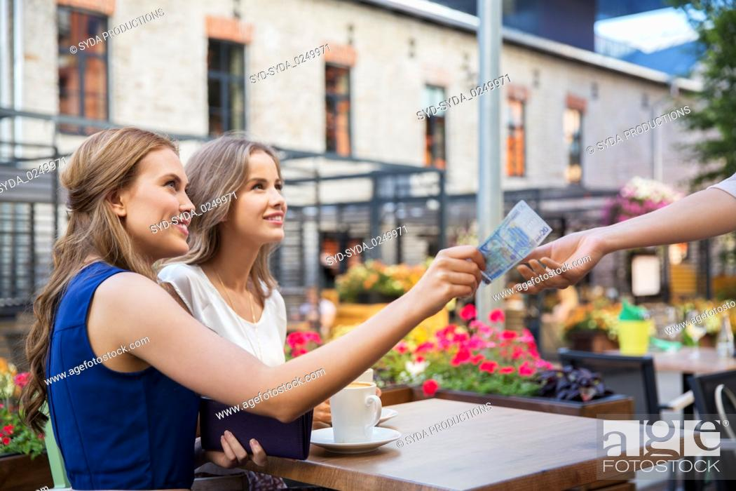 Stock Photo: young women paying for coffee at street cafe.