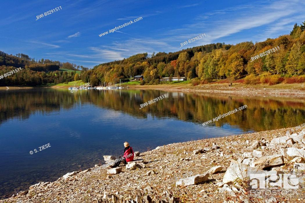 Stock Photo: woman sitting at the lakefront of Henne storage lake and enjoying a good view, Germany, North Rhine-Westphalia, Sauerland, Meschede.