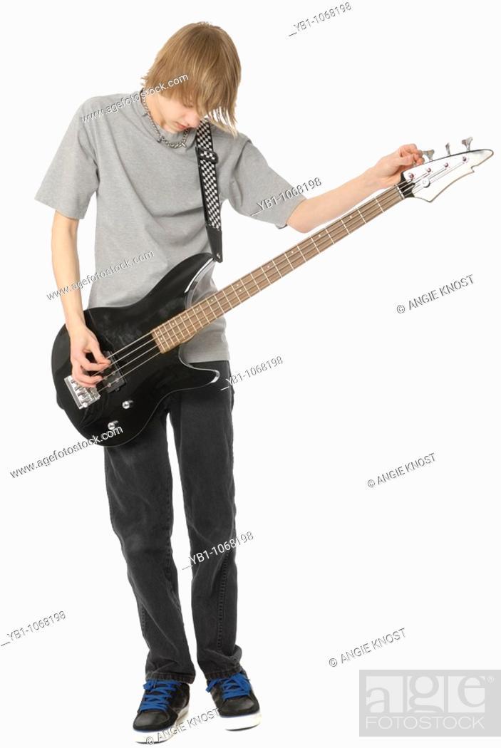 Stock Photo: Teenage boy tuning his bass guitar.