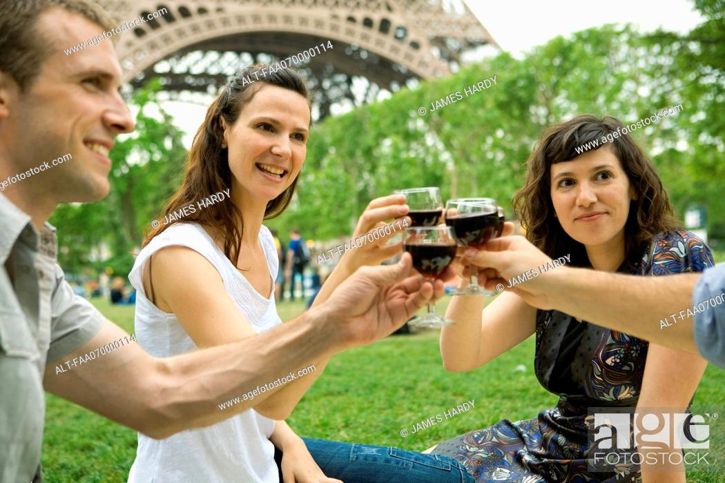 Stock Photo: Friends clinking wine glasses outdoors.