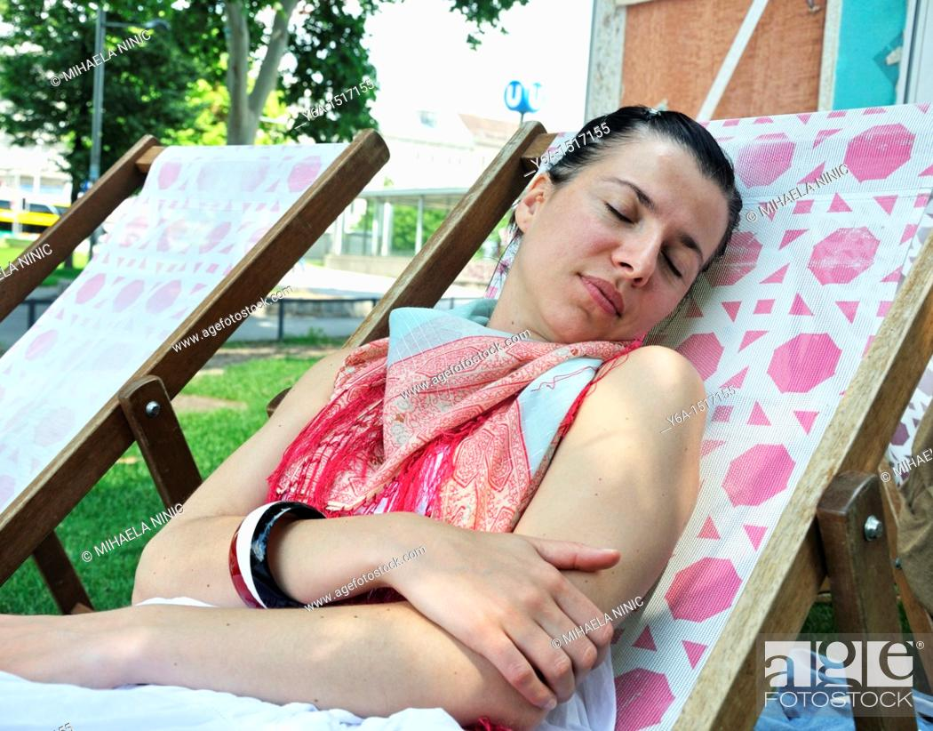 Stock Photo: Young woman resting on lounge chair in outdoor cafe in Vienna.