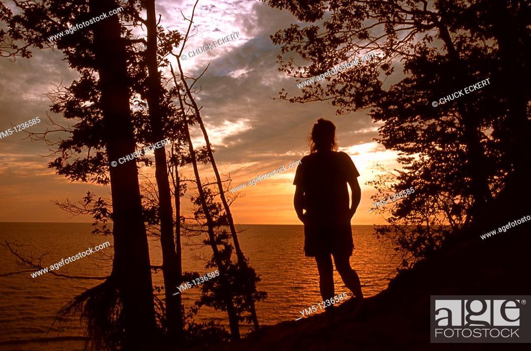 Stock Photo: Woman hiking along Lake Michigan sand dune at sunset.
