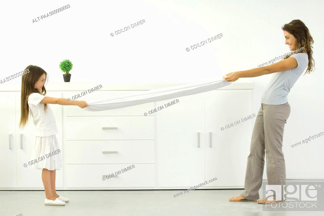 Stock Photo: Mother and daughter pulling on opposite ends of sheet.