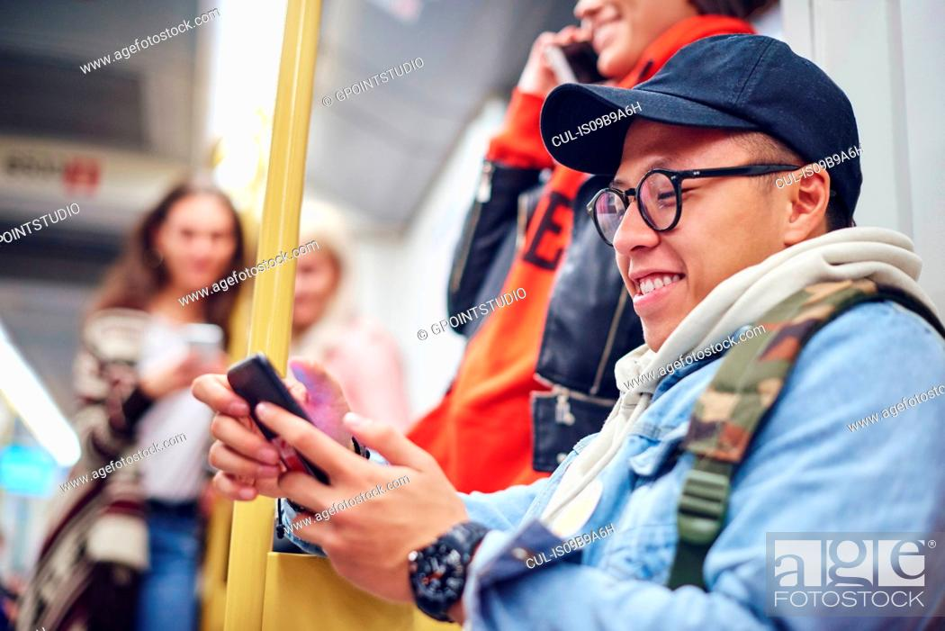 Stock Photo: Young man looking at smartphone on city tram.