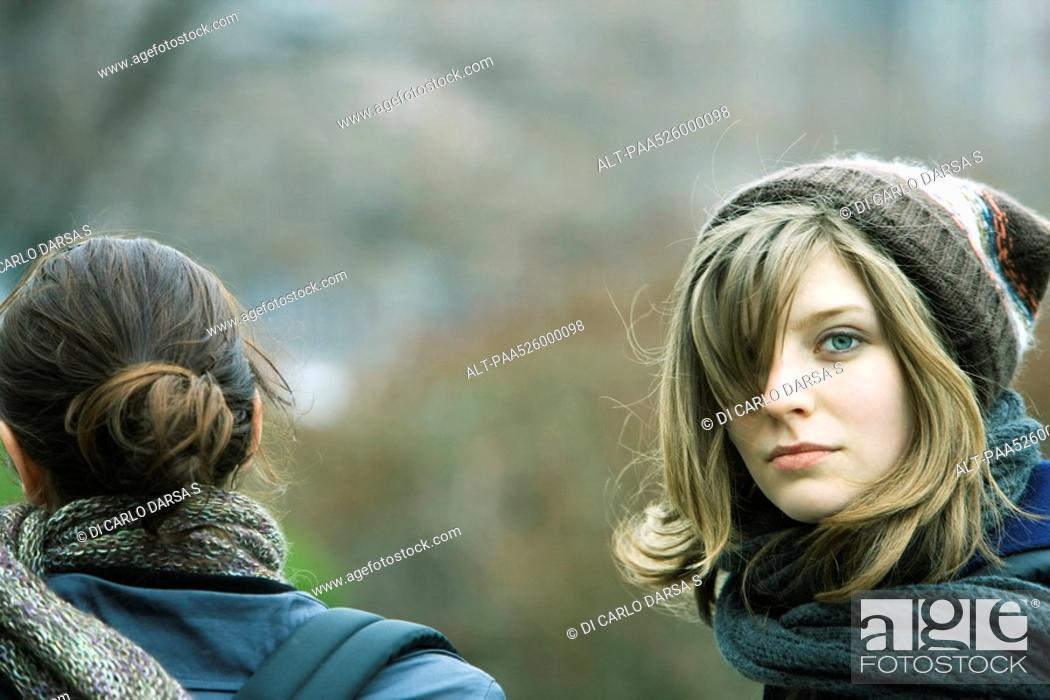 Stock Photo: Young woman walking with friend in park, looking over shoulder at camera.