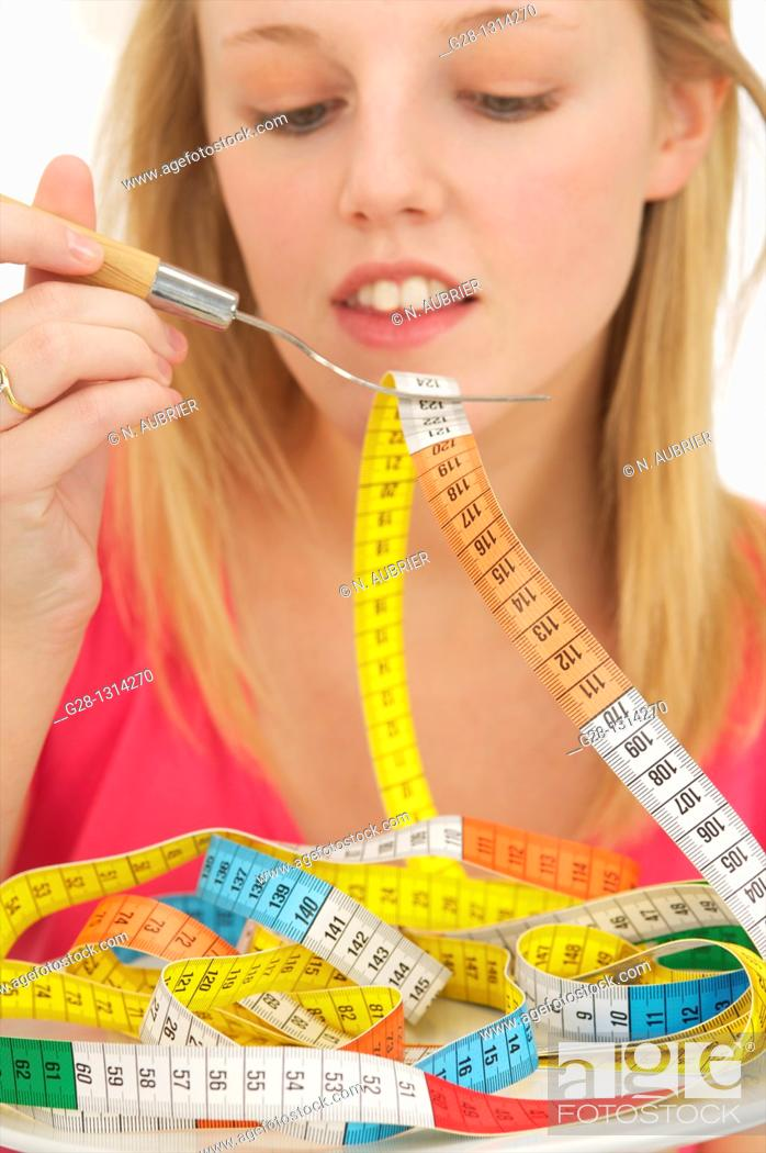 Stock Photo: Young blond woman with long hair eating a colored tape out of a plate to evoke the concept of diet and weight problems, concept image.