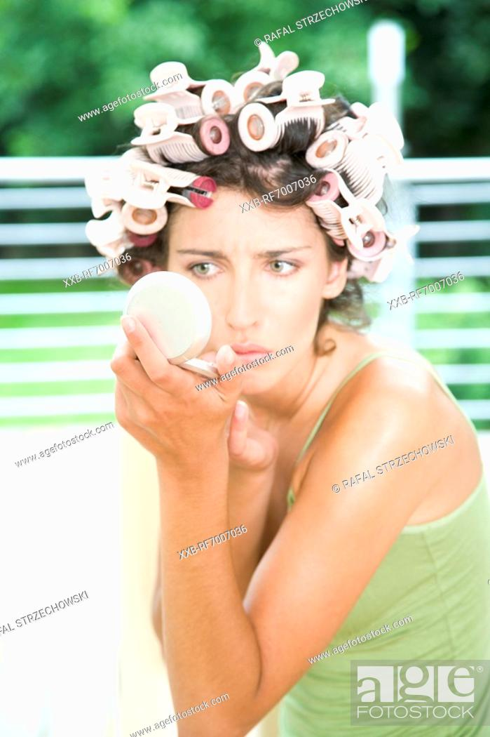 Stock Photo: Young woman doing make up.