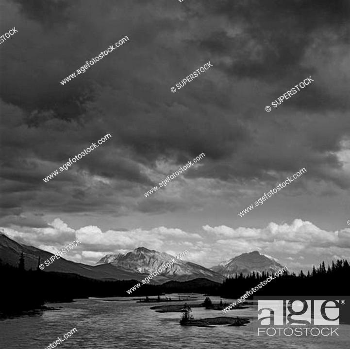 Stock Photo: River passing through a forest with mountains in the background, Athabasca River, Mt Kerkeslin, Jasper National Park, Alberta, Canada.