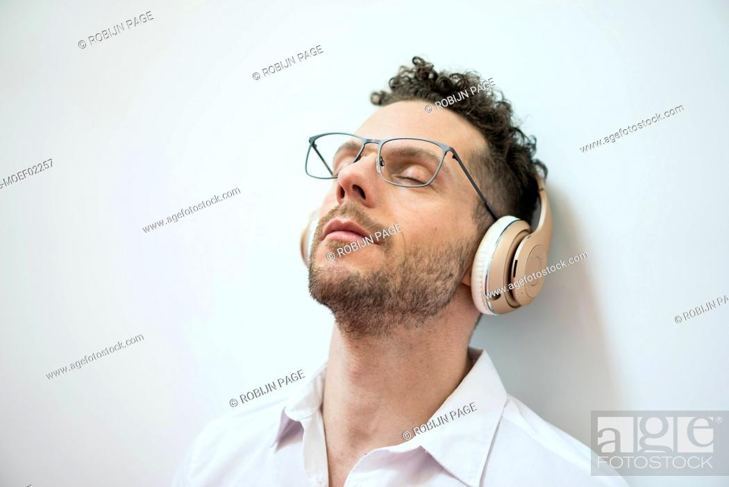 Stock Photo: Businessman with closed eyes listening to music with headphones.