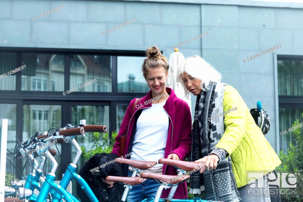 Stock Photo: Mature woman and daughter looking at city bicycles at bike park.