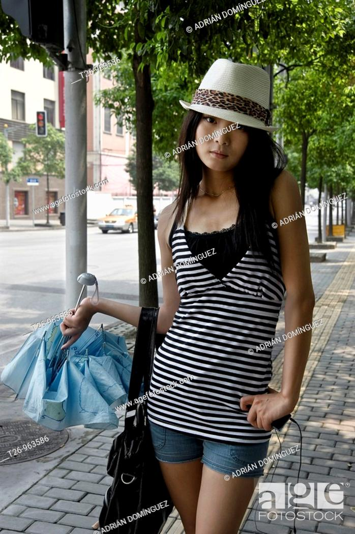 Stock Photo: Girl poses before the camera on a street in Shanghai, China.