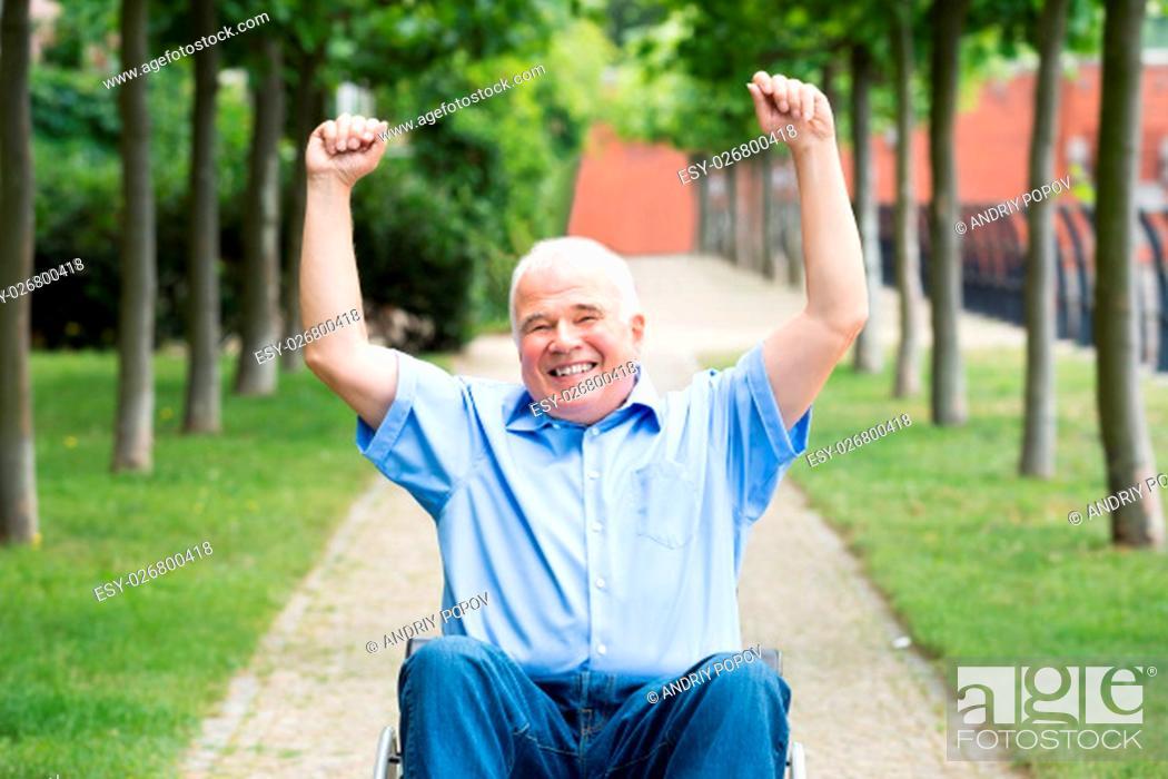Stock Photo: Happy Senior Man On Wheelchair With Arm Raised.