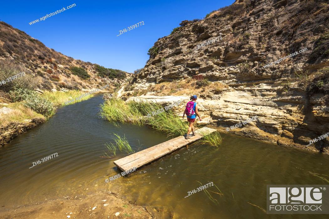 Stock Photo: Hiker crossing the stream at Water Canyon, Santa Rosa Island, Channel Islands National Park, California USA.