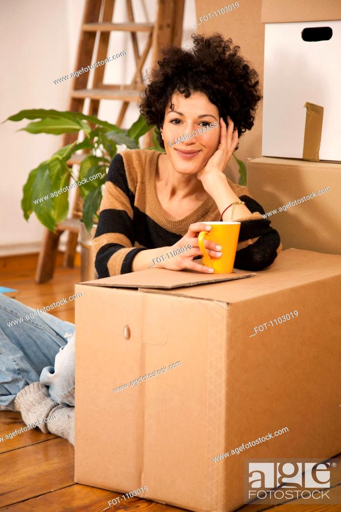 Stock Photo: A cheerful woman taking a coffee break while moving house.