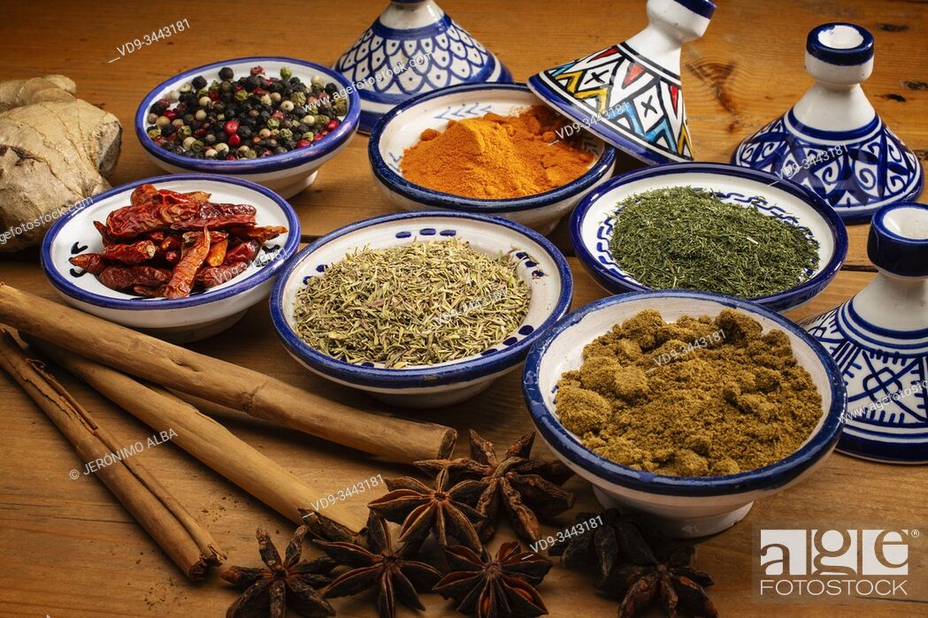 Stock Photo: Healthy food. Spices in ceramic containers typical of Morocco on an old wooden table. Colored pepper, curcuma, cayenne, cinnamon, ginger, cumin, star anise.