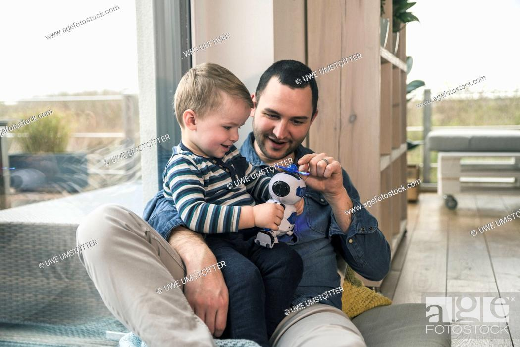 Stock Photo: Father and son playing with a toy robot at home.
