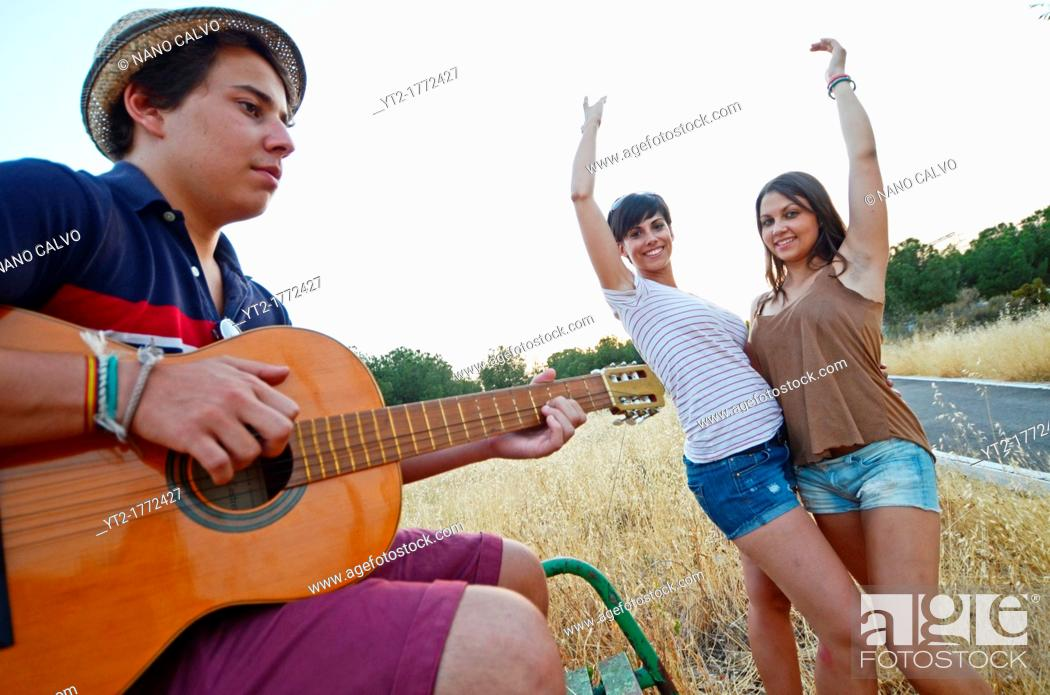 Stock Photo: Young man plays the Spanish guitar while her friends dance Sevillanas.