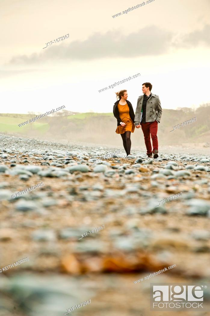 Stock Photo: A young couple, boyfriend and girlfriend, together on a windy afternoon on the seashore, west wales UK.