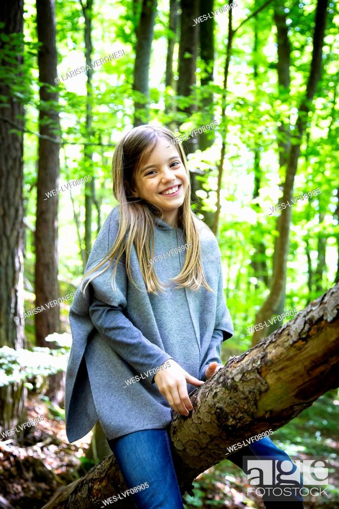Photo de stock: Portrait of smiling cute girl sitting on tree trunk in forest.