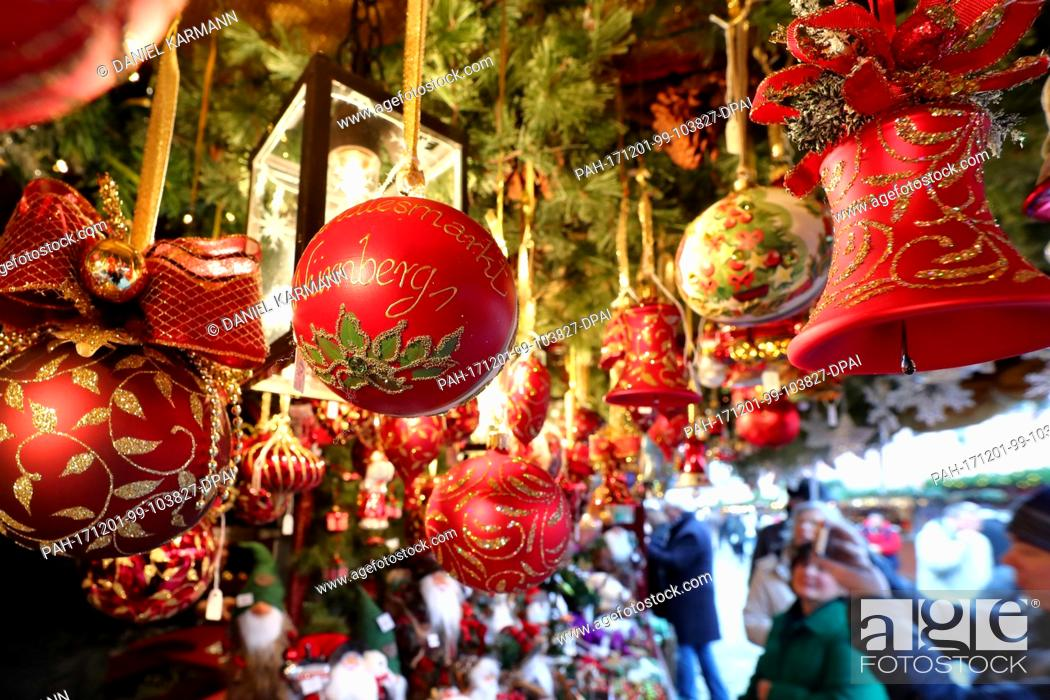 Stock Photo: Red Christmas balls hang from a stand at the Nuremberg Christmas market in Nuremberg, Germany, 01 December 2017. Photo: Daniel Karmann/dpa.