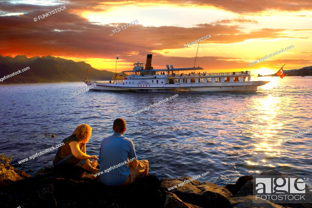Stock Photo: Youg couple watching a ferry at sunset on Lac Leman lake Geneva - Montraux Switzerland.