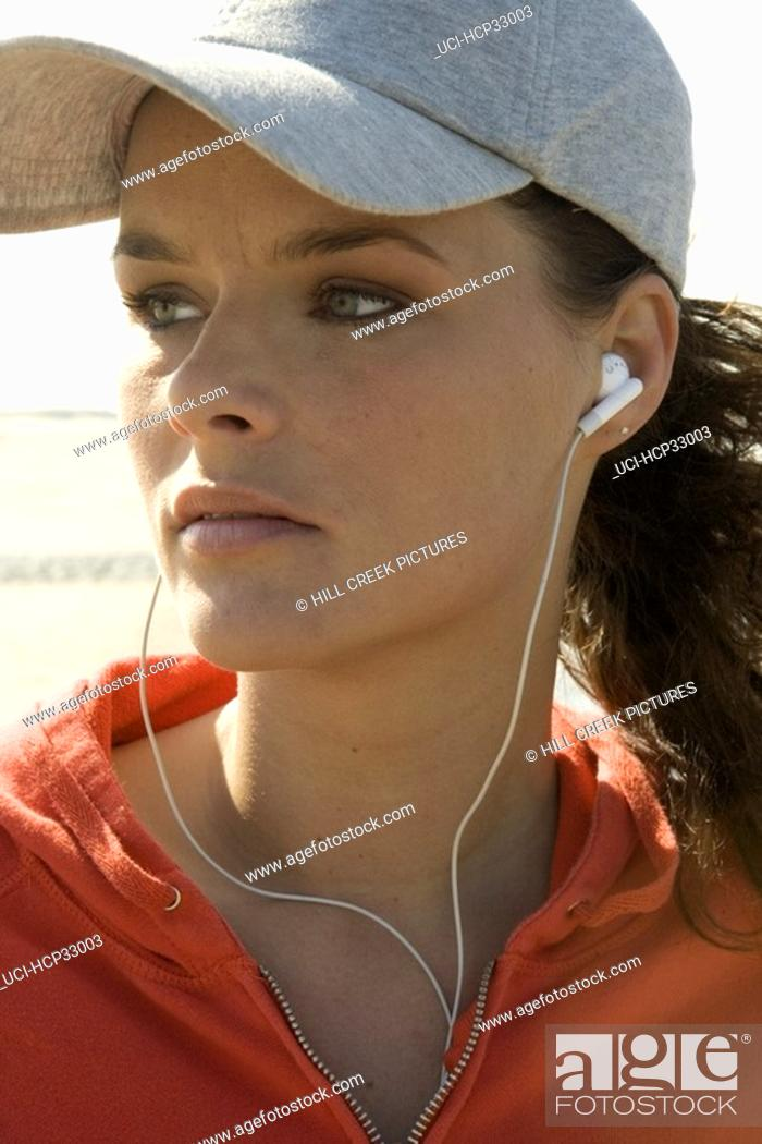 Stock Photo: Young woman listening to earbuds, wearing baseball cap.