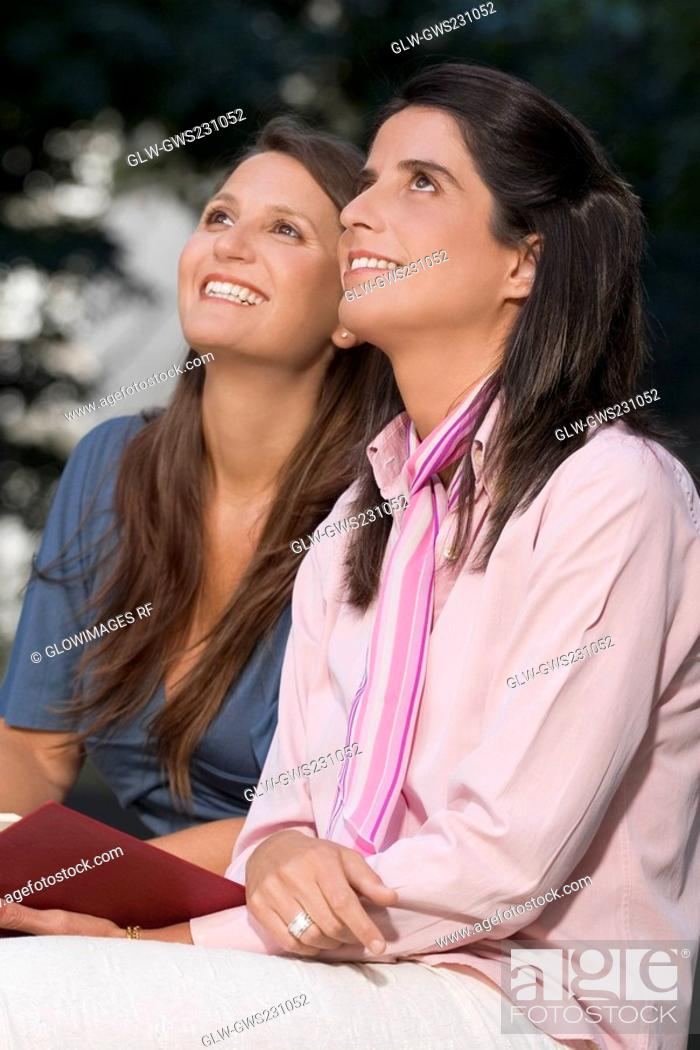 Stock Photo: Side profile of two mid adult women sitting together and smiling.