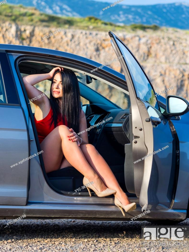 Stock Photo: Attractive young woman in a car in countryside in late afternoon exposing legs in high-heels.